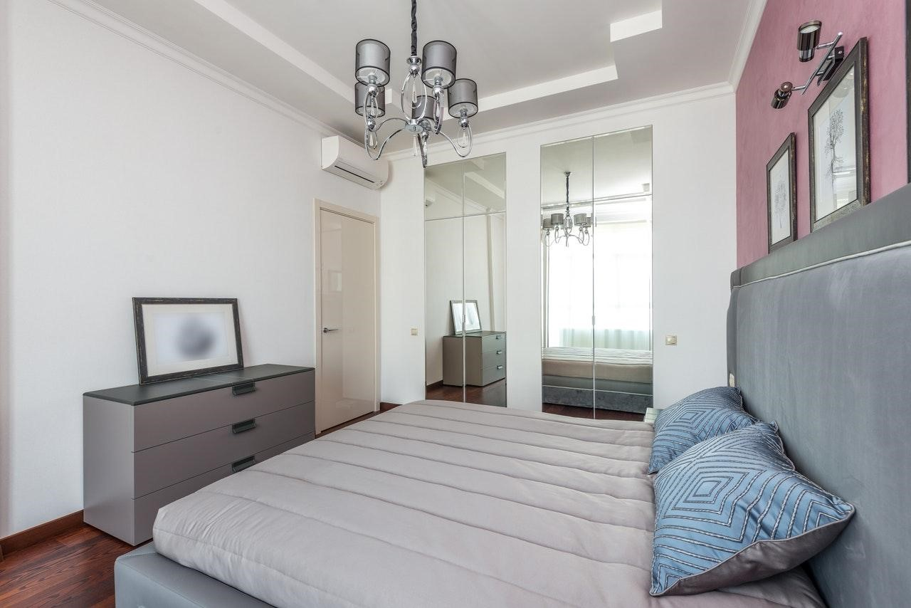 Прихована дзеркальна шафа в спальні мінімалізм