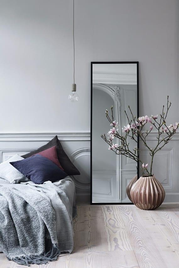 Сіра спальня в стилі мінімалізм з вазою на підлозі